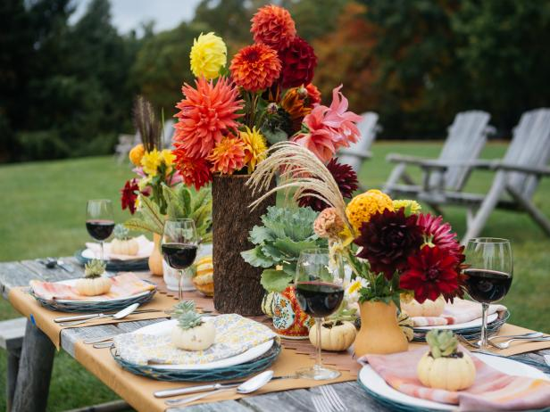 An outdoor table is topped by a gorgeous fall centerpiece and table setting.