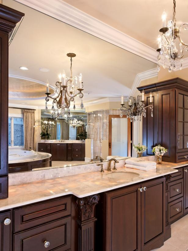 Neutral Bathroom With Wood Vanity, Large Mirror and Chandelier