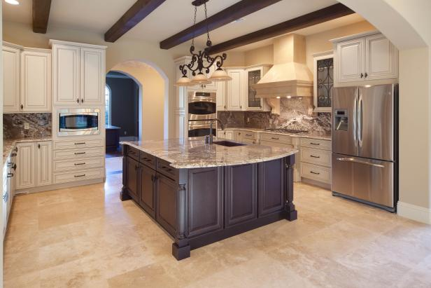 Neutral Mediterranean Kitchen With Large Island and White Cabinets