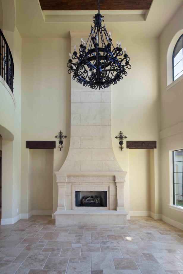 Neutral Living Room With Travertine Fireplace and Old World Chandelier