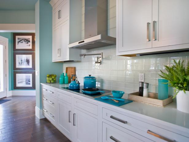 Kitchen With White Cabinetry, White Tile Backsplash & Stainless Hood