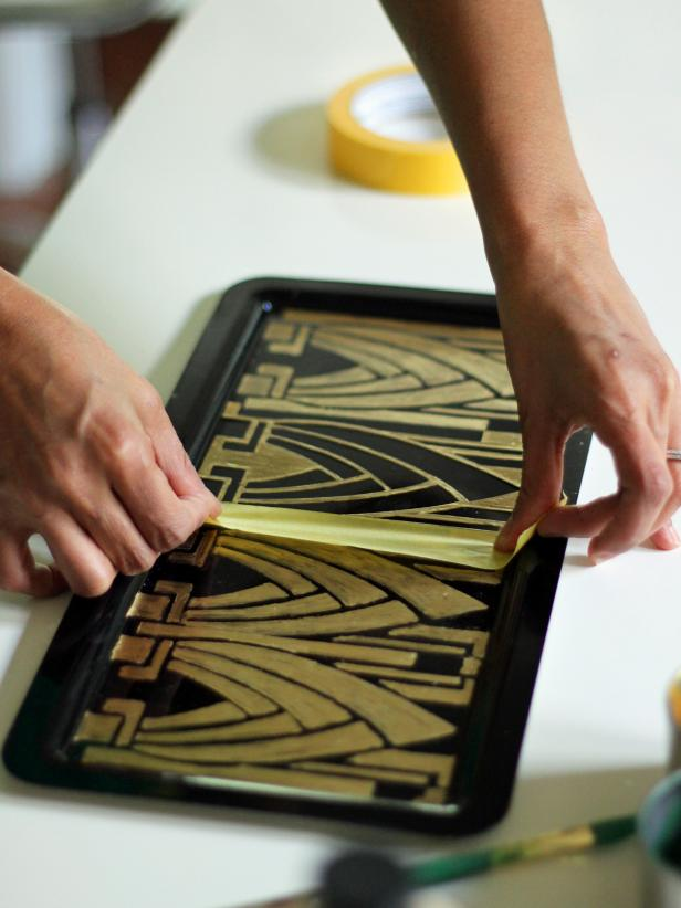 Letting the paint dry completely on each section of the tray before removing the stencil and painter's tape is step 4 in creating an Art Deco vanity tray. If you pull the tape up before the paint is completely dry, the tape might pull the paint from the surface of the tray.