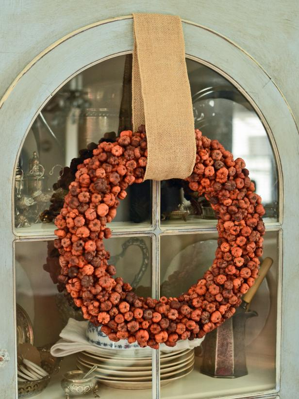 Once all pods are glued in place, use your fingers to gently remove any strings left by hot glue. Loop a wide ribbon around completed wreath to hang indoors or out.