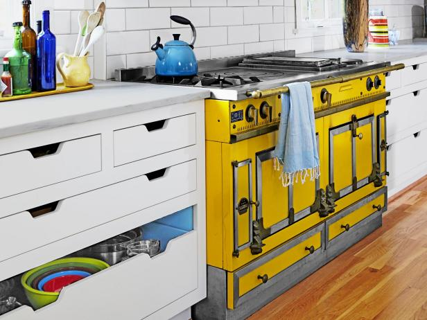 A yellow stove range with a white storage cabinet.