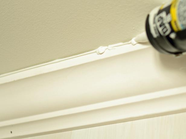 Caulking is one of the finishing touches to installing custom jobs. Fill nail holes and small seams with wood filler. Place a small amount on your fingertip and rub over a hole or seam. Using a caulk gun, apply paintable trim caulk to seams, crown and trim. Run a small bead along the seam and smooth with a wet finger or cotton cloth. Allow caulk and wood filler to dry. Sand any rough areas with heavier grit (lower-numbered) sandpaper, working to fine grit.