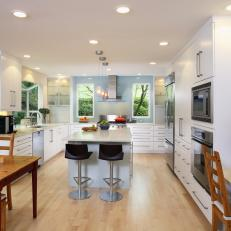 Contemporary White Kitchen With Island and Black Bar Stools