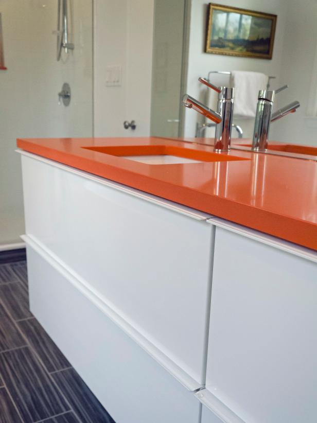 White Vanity With Clean Lines and Orange Countertop With Faucet
