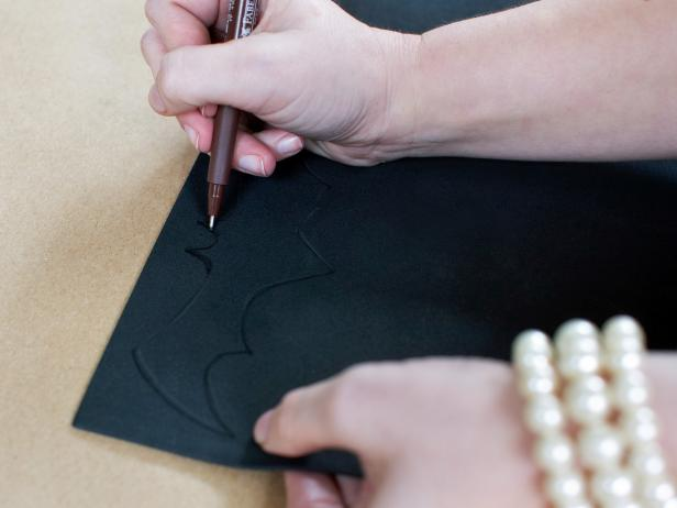 Trace or freehand the silhouette of a bat onto craft foam with black pen or marker then cut out silhouette with scissors. Repeat the process to make multiple bats in assorted sizes.