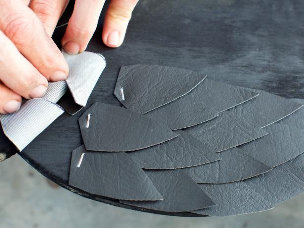 After the paint is dry, cut approximately 25 leaf-shaped feathers for each own from black vinyl. Layer them along each side of the owl silhouette, attaching them with staple gun.