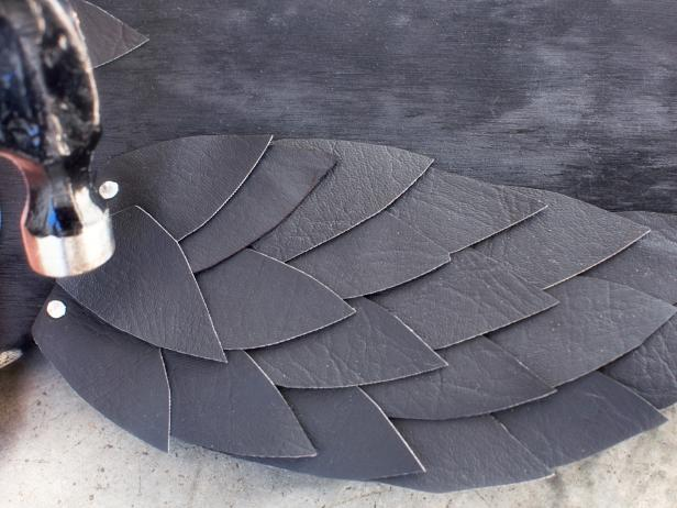 Using hammer, add a decorative row of stainless steel tacks along the top row of feathers.