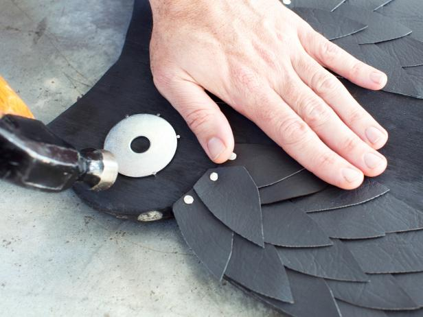 Position washers along face area of owl silhouette. Once in place, attach with picture nails around the perimeter and fastened in place with hammer.