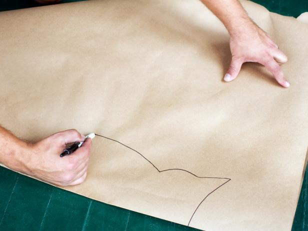 Place a sheet of brown kraft paper onto a flat, level surface then fold it in half. Freehand the silhouette of an owl to the size and scale you'd like using a pen or marker