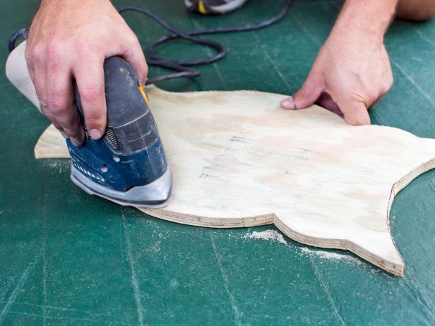 Using an orbital sander, smooth any flaws or rough spots in the plywood.