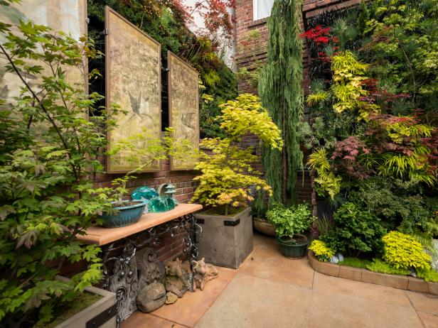 Asian Courtyard Garden With Potted Trees and Artwork