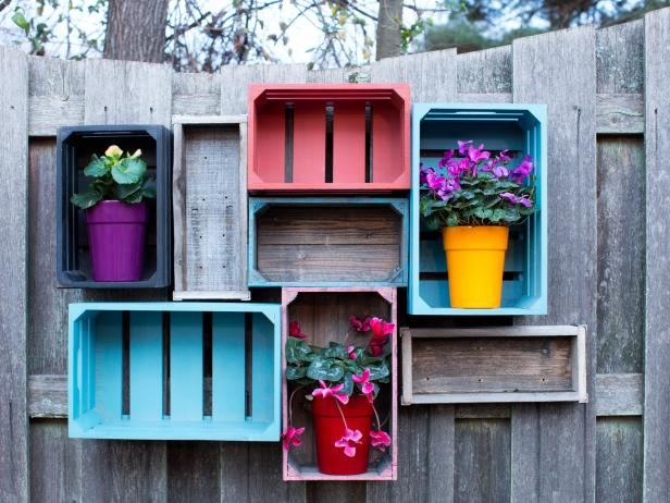 Colorful Wooden Crates Holding Potted Flowers Attached to Wooden Fence