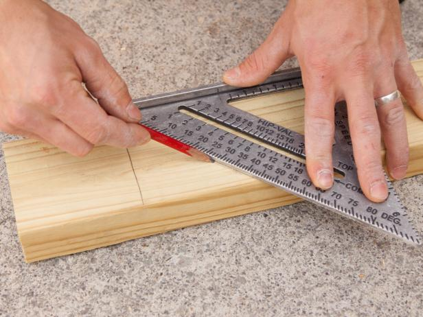 A ruler and a pencil are used to measure and mark a piece of wood.