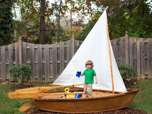 This backyard features a sandbox sailboat ready for adventures.