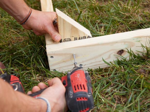 Using exterior coated wood screws, secure one spike into each of the four corners of the box frame.