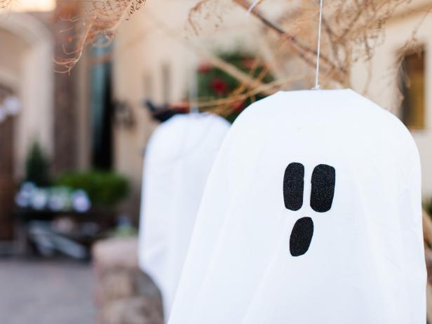 Attach your ghosts with hot glue or fabric glue then hang your ghost from a low tree limb, light post or shepherd's hook.