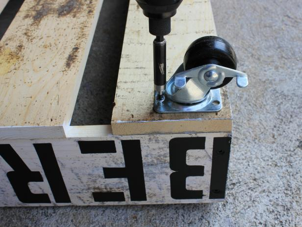 Arrange four casters along the bottom wood planks, spaced roughly three inches in from each of the four edges. Use a drill to create a hole for each, then screw them securely in place using a drill or screw gun.