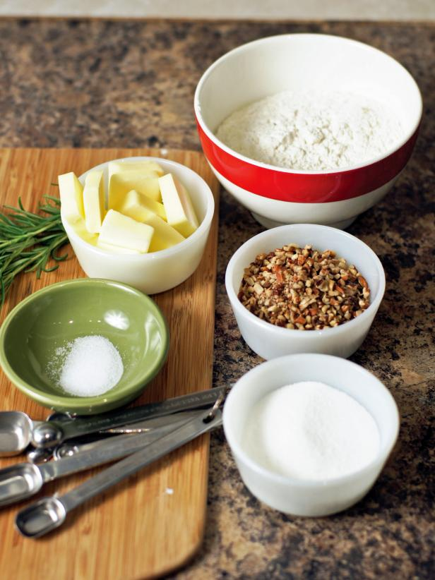 The first step is to gather ingredients for the nut crust including flour, sugar, pecans, salt, butter, egg yolk and fresh rosemary.