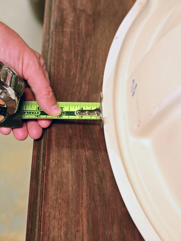 The area for a sink installation is measured on a vintage dresser.