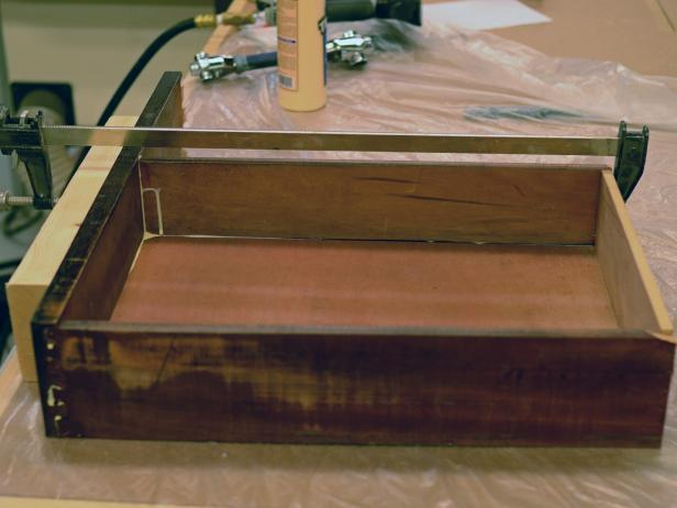 A drawer from a vintage dresser is clamped to aid in glue drying after being cut for use in a bathroom vanity.
