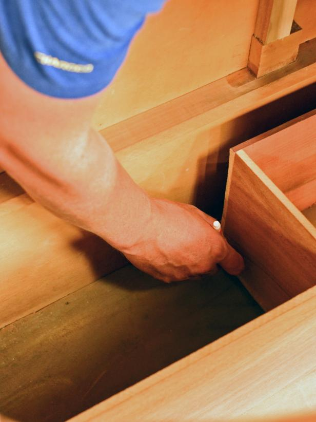 A drawer in a bathroom vanity custom built from a vintage dresser is measured for fit.