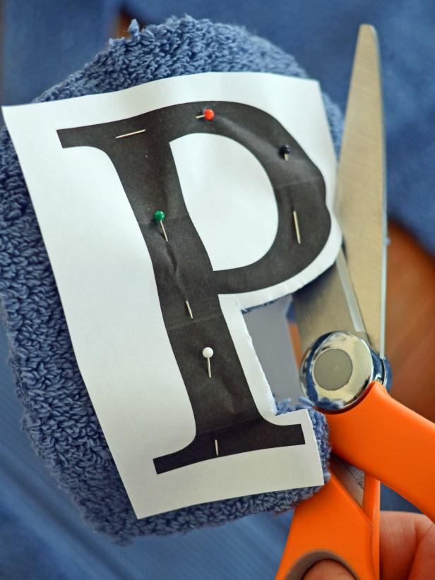 Use sharp scissors to cut around letter, leaving about 1/4-inch border. Remove pins and paper from letter. Trim and clean edges with scissors, if necessary. Tip: Select a block letter style. A font with lots of curves, details and skinny lines will be hard to cut and sew.