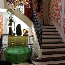 Grand Staircase with Orange Geometric Shape Wallpaper and Gold Chandelier