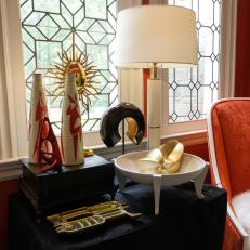 Side Table With Eclectic Objects in Bold Orange Room