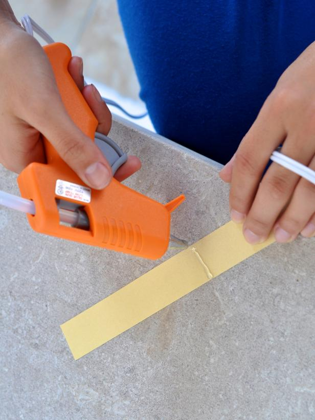 One of the first steps is to heat up your hot glue gun. Add a line of hot glue to back of paper strip.