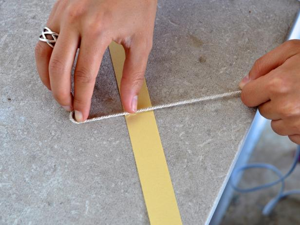 The next step is to press twine along line of hot glue that you applied to the card stock strip.