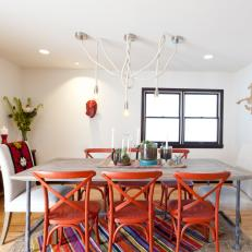Eclectic White Dining Room with Orange Chairs