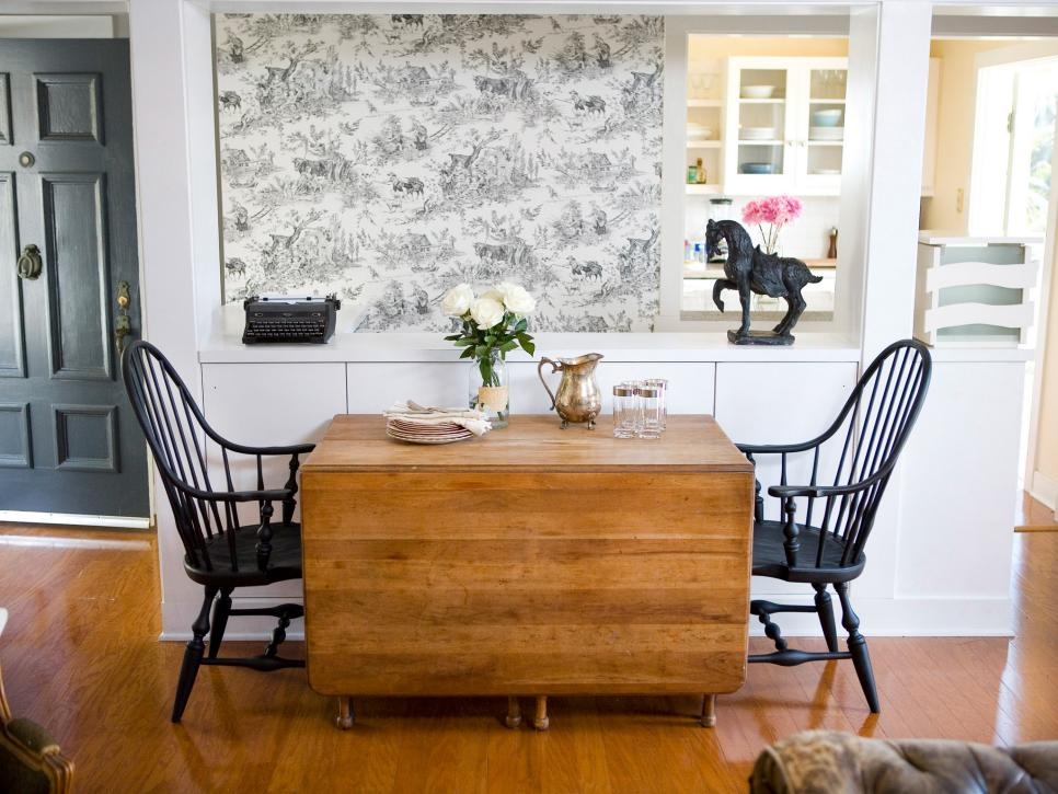 Rustic dining table and toile wallpaper mesh with black Windsor chairs