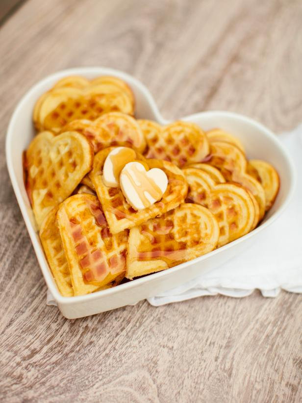 Wake up your loved one with fluffy, heart-shaped homemade waffles covered in sweet maple syrup.