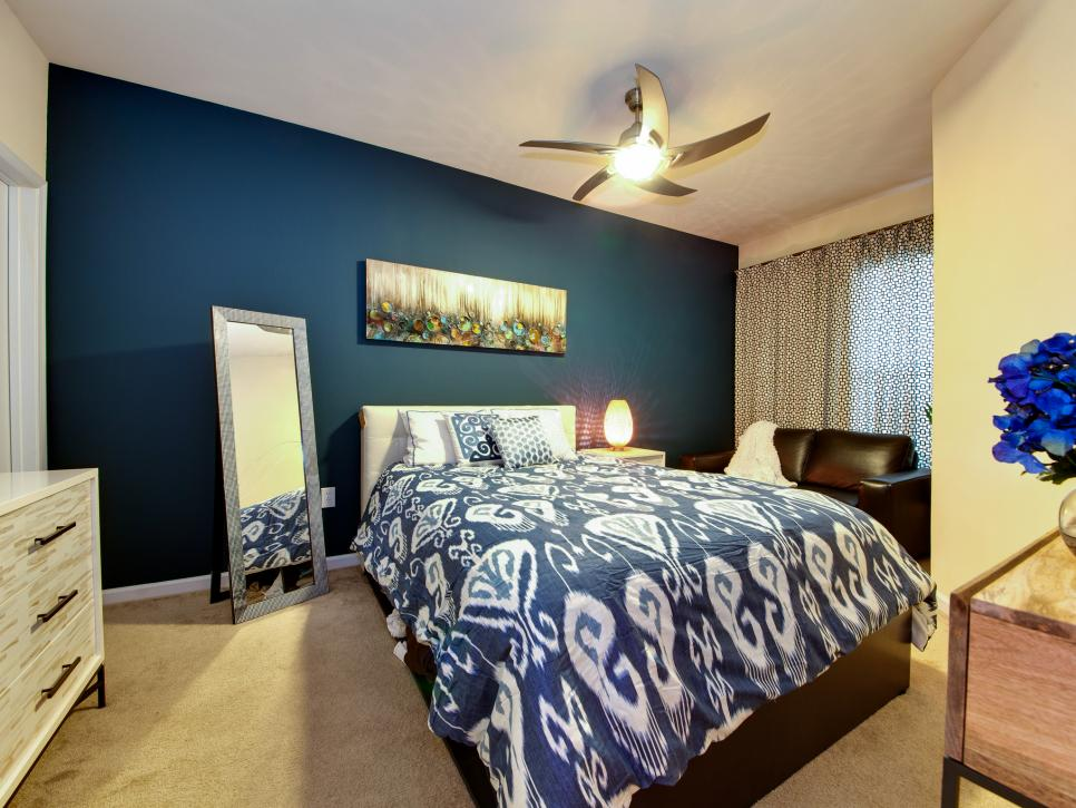 Small Angular Bedroom with Blue Accent Wall and Ikat Bedding