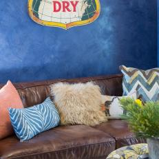 Textured Blue Living Area With Brown Leather Sofa and Vintage Metal Sign