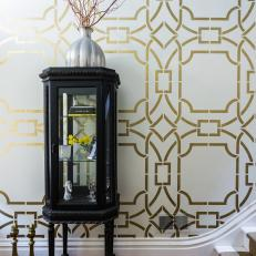 Dramatic Entryway With Metallic Stenciled Wall and Vintage Curio Cabinet