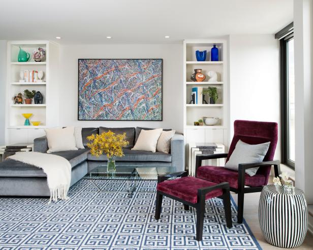 This sleek and modern living room features built-shelving that flanks a comfy gray sectional, while a blue and white Greek key patterned rug anchors the space. A velvet maroon chair and ottoman add a pop of color, pattern and texture to bring the small living room to life.