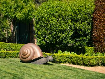 Eclectic Garden Featuring a Large Snail Sculpture