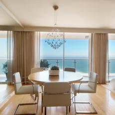 Neutral Modern Oceanfront Dining Room With Wall of Mirrors