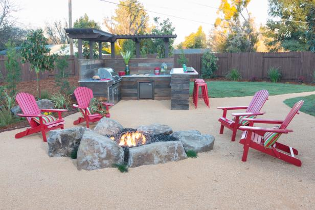 Outdoor Kitchen Next To Rugged Stone Fire Pit With Red Chairs