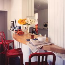 Breakfast Bar With Cutout Window and Tall Red Barstools