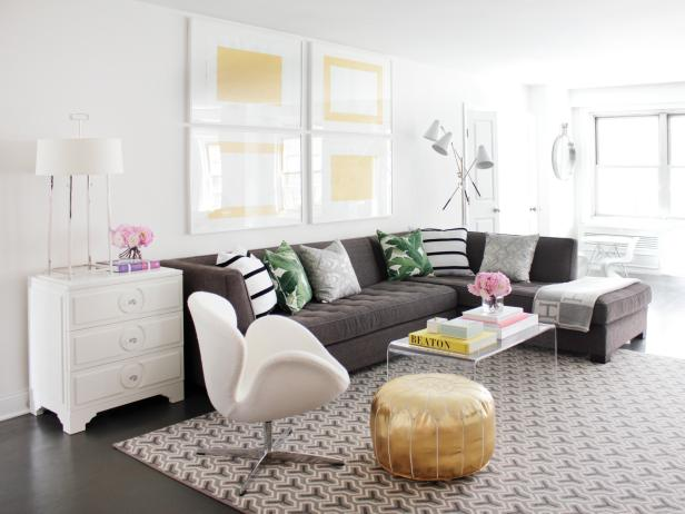 Cool, soothing grays provide contrast against fresh white walls and furnishings in this contemporary living room. A charcoal sectional supplies ample seating, and pillows in fun, lively patterns add personality.