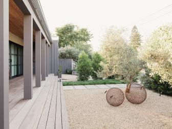 Gravel Courtyard With Gray Deck and Globe Sculptures