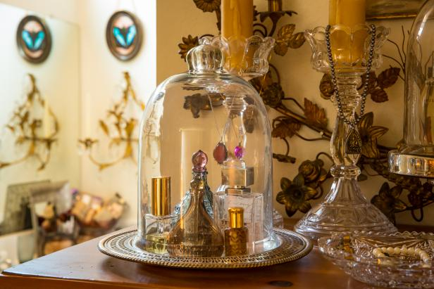 Perfume Bottles in Glass Bell Jar and Glass Candlesticks on Dresser