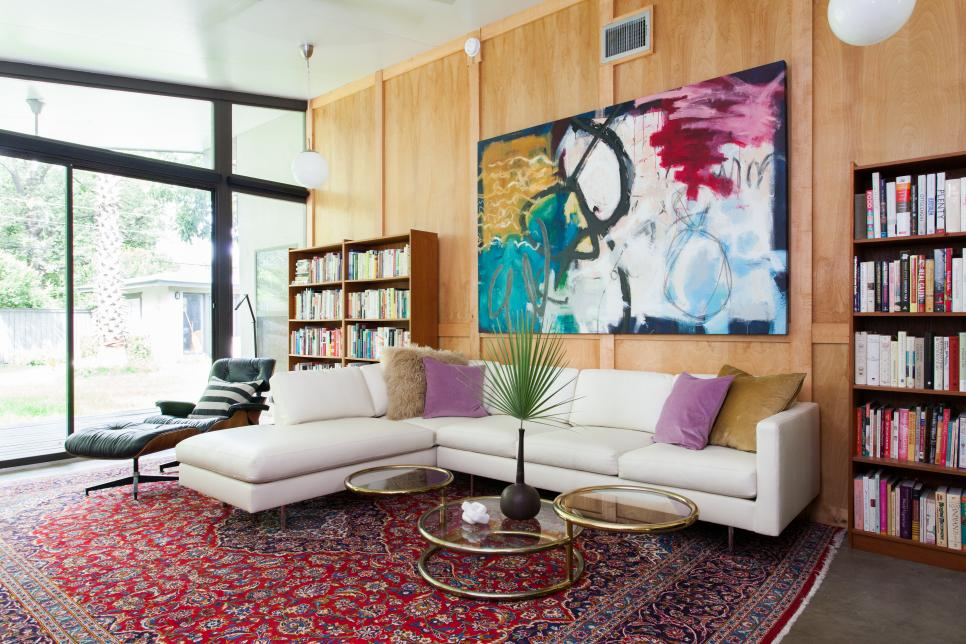 Transitional Family Room With Red Area Rug, White Sectional & Mod Art