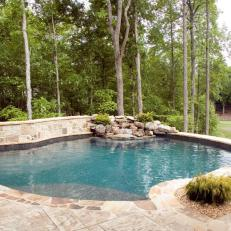 Swimming Pool With Rustic Waterfall and Stone Retaining Wall