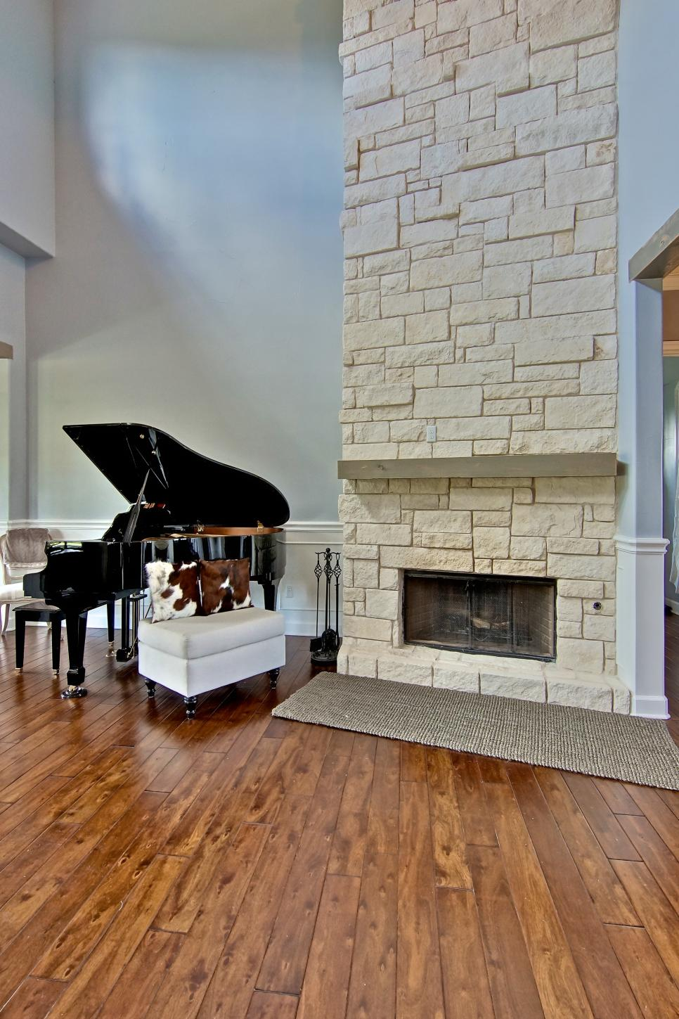 Gray Living Room With Limestone Fireplace, Piano & Cow Hide Pillows